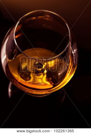 Top Of View Of Snifter Of Brandy In Elegant Typical Cognac Glass On Dark Background With Golden Refl