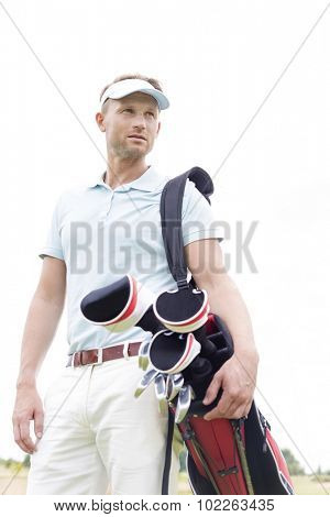 Low angle view of thoughtful mid-adult man carrying golf club bag against clear sky