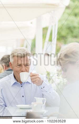 Middle-aged man looking at woman while having coffee at sidewalk cafe