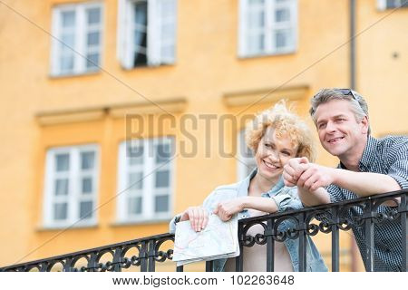 Happy middle-aged couple with map leaning on railing against building