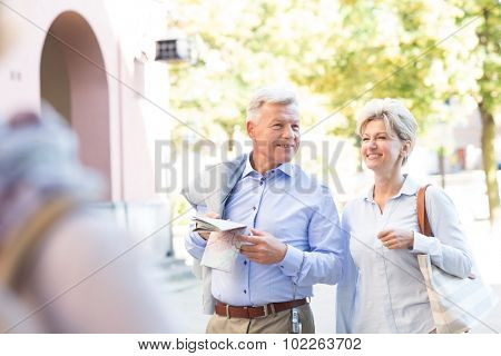 Happy middle-aged couple with map walking in city