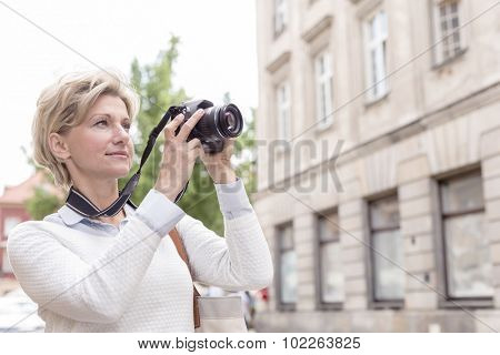 Middle-aged woman photographing through digital camera in city