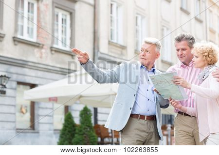 Man assisting to middle-aged couple with road map in city