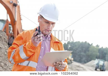 Supervisor reading clipboard while using walkie-talkie at construction site