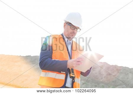 Male supervisor reading clipboard at construction site on sunny day