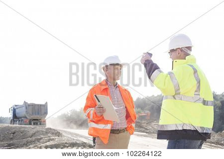 Supervisors discussing at construction site against clear sky