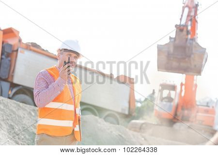Architect using walkie-talkie while working at construction site
