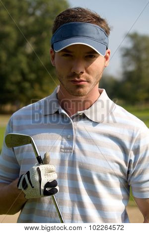 Portrait of young man holding golf stick