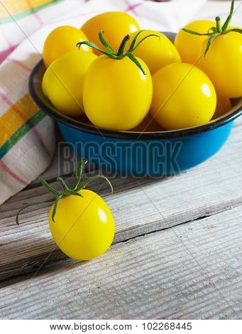 Organic Yellow Cherry Tomatoes With Water Drops In Blue Bowl