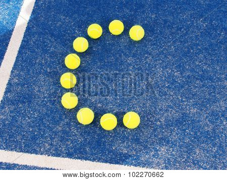 Tennis ball in shape of letter C on a blue artificial grass