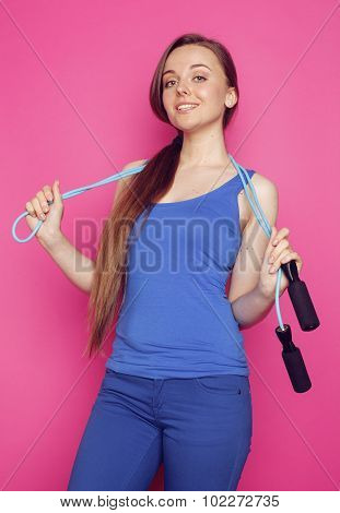 young happy slim girl with skipping rope on pink background smiling