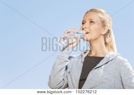 Young girl drinking water after morning run