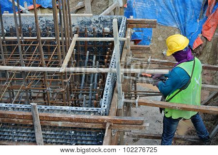 Construction workers installing pile cap formwork made from polymer at the construction site.
