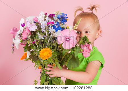 Portrait toddler girl with bouquet garden flowers on pink background
