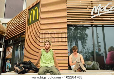 NICE, FRANCE - AUGUST 15, 2015: young man sit near McDonald's restaurant. McDonald's is the world's largest chain of hamburger fast food restaurants, founded in the United States.