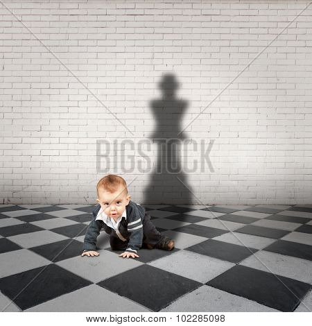 little boy with king shadow on a checkered floor