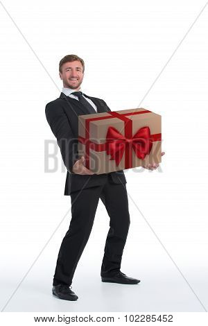 Smiling businessman carrying heavy present