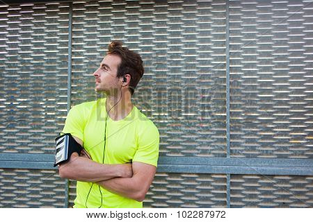Attractive man enjoys a wonderful morning after intense fitness training while listen to music