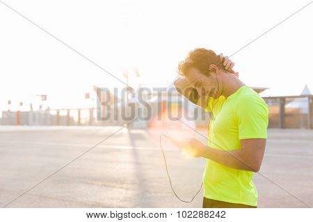 Male runner uses a mobile phone to switch music on the playlist with copy space for text advertising