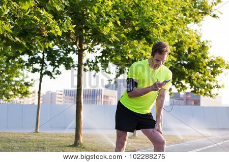 caucasian male jogger choosing music on playlist while having rest during daily run