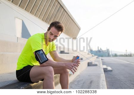 Male runner with bottle of water in the hands having rest after workout outside city