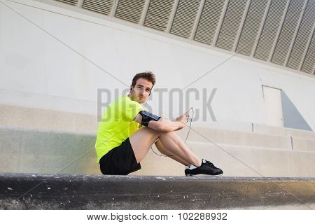 Young sports man with mobile phone in the hand sits on steps taking break
