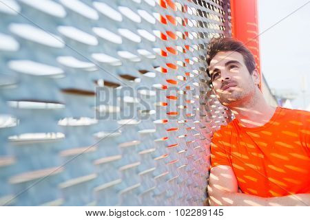 Portrait of caucasian sad man leaning on metal fence with hands crossed looking thoughtful