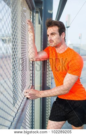 Portrait of caucasian sports man standing near metal fence thoughtful looking away while rest