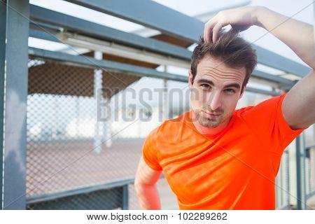 Sports build caucasian man taking break after evening run in urban setting