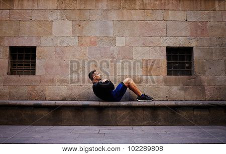 Young muscular build man doing crunches outdoors in antique city