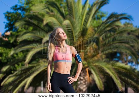 young female jogger closed her eyes enjoying the sun and rest after morning run