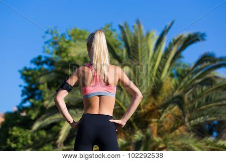 Young woman dressed in sports wear resting after fitness training outdoors