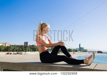 Young beautiful fit woman resting after jog in the fresh air