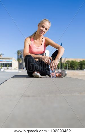 Young female runner resting after workout outdoors