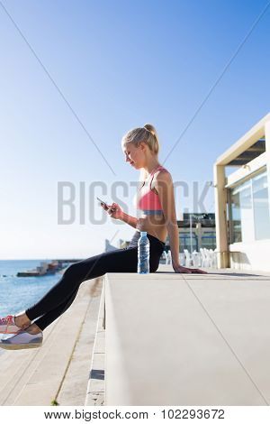 Fit women chatting on mobile phone while resting after run