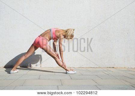 Woman in sportswear stretching legs against street wall with copy space for text