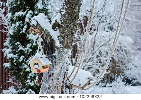 bird feeder in winter garden with trees covered with snow