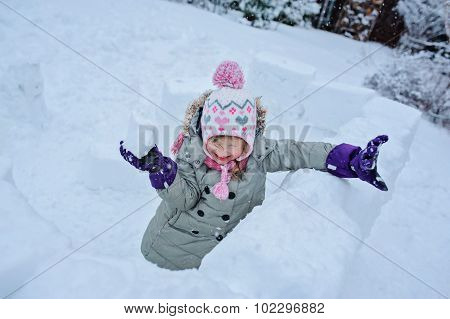 happy child girl playing with snow castle and dropping snowballs at winter backyard