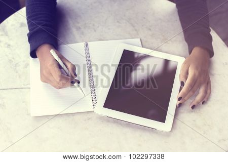Girl Writes In A Notebook And Working With Digital Tablet