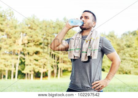 Young Man Drinking Water From A Bottle After Workout