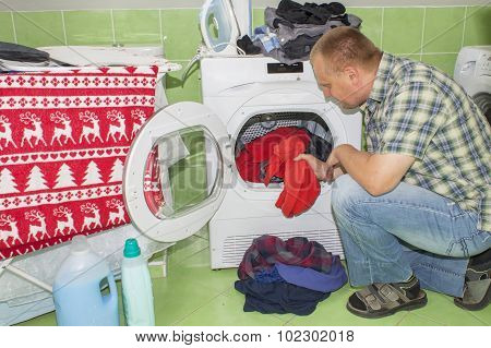 Man washes clothes in the washing machine. Housework men.