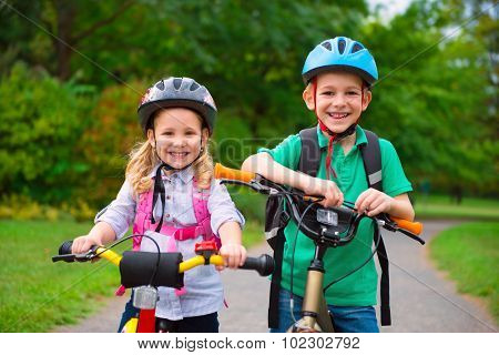 Two Children Cycling In Park