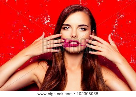 Beautiful Model On A Red Background Rubbing Lipstick