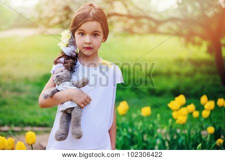 adorable dreamy child girl in spring flowering park with teddy bear