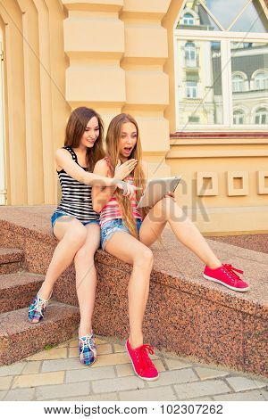 Two Beautiful Surprised Girls Sit On Parapet And Look To Tablet
