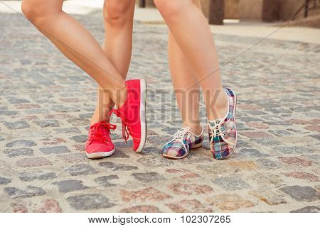 Young Women Walk In Sneakers On The Pavement