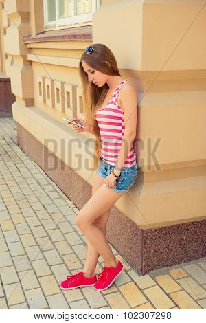 Beautiful Girl Reads Sms Standing Near The Building