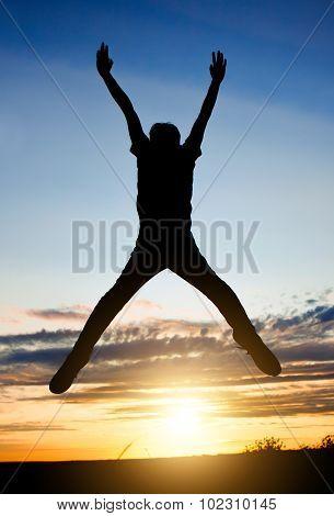Happy Man Jumping At Sunset