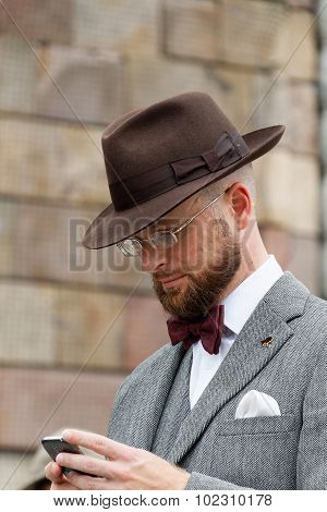 Man Wearing Hat And Tweed Looking At His Phone