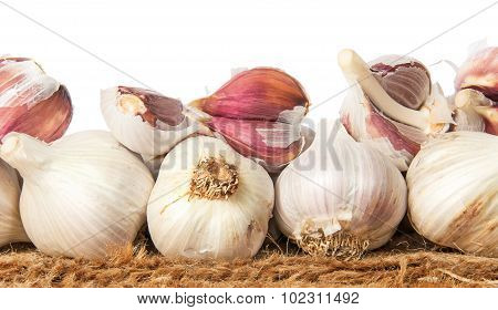 Pile Of Whole And Cloves Of Garlic On Sackcloth